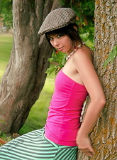 Ariel Rebel reveals her playful nature by dancing near a tree in the local forest.
