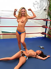 Horny dyke chicks Charlie Laine and Melissa Jacobs wrestle and fuck in the ring.