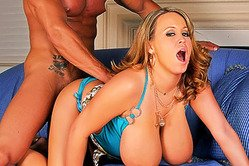 Brandy Taylor holds her massive round jugs as her lover stabs his cock between them.